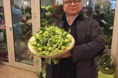 Игорь Угольников с солнечным букетом из тюльпанов, гиацинта, хризантемы кустовой, ранункулуса и скиммии.
